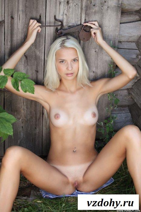 Блондинка на траве возле деревянной двери.