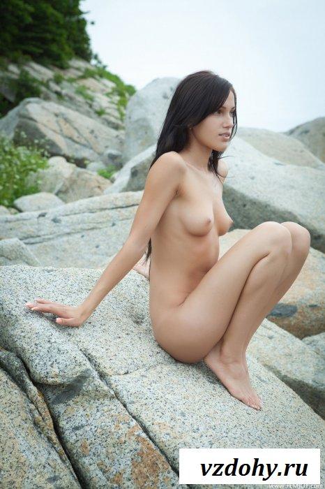 Молодая брюнетка на больших камнях.