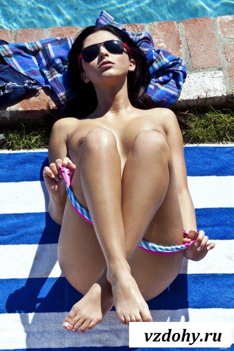 Студентка возле бассейна на полосатом матрасе.