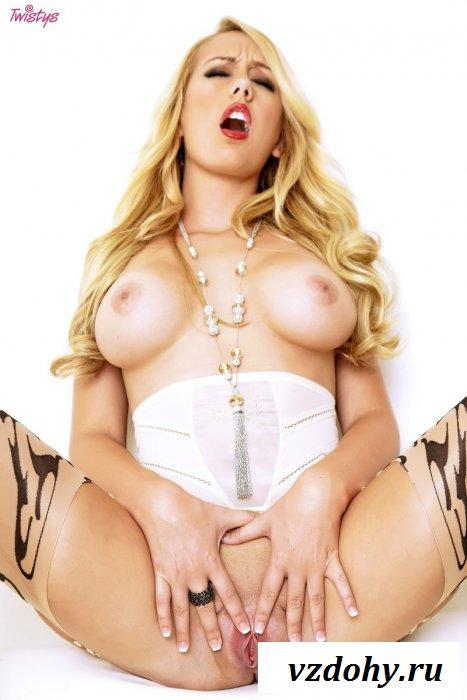 Сиськастая блондинка на белом диване.