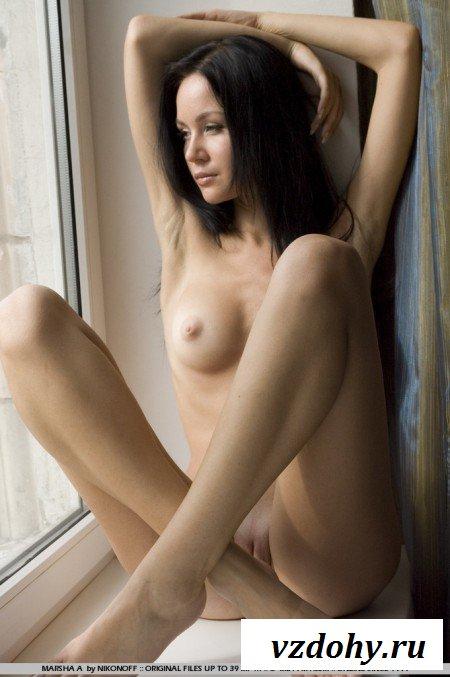 Милая брюнетка сидит на подоконнике