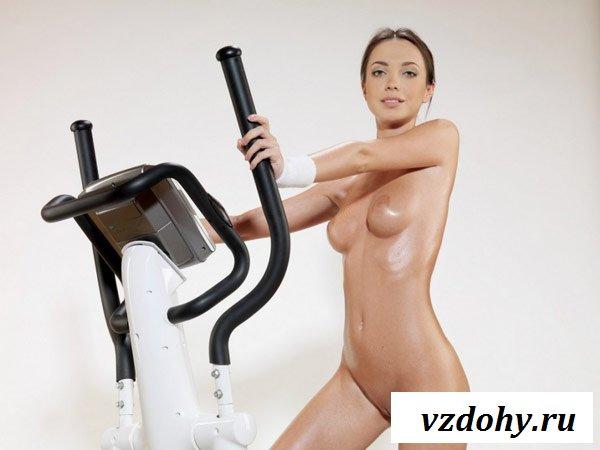 Обнажённая спортсменка занимается на тренажёре