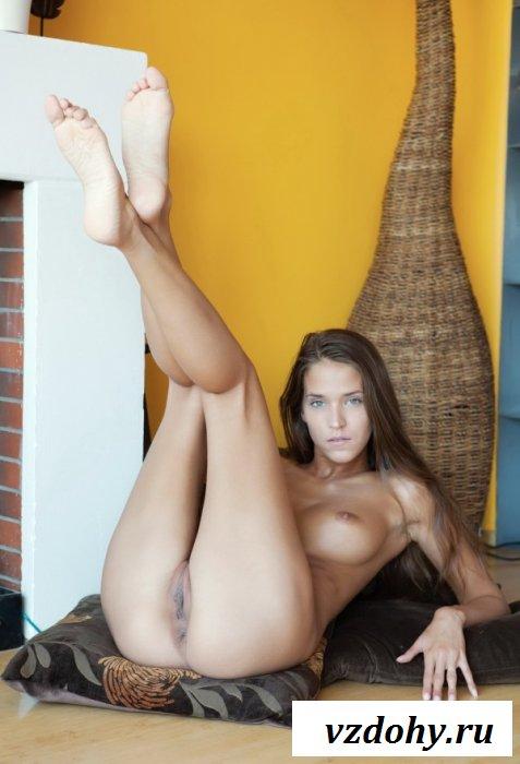 Девка искушает своими ножками возле камина