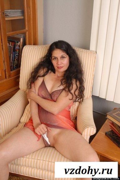 На кресле обнажённая зрелая женщина