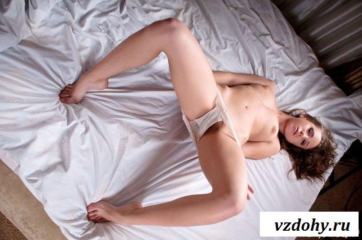 Обнаженная барышня делает фото в постели