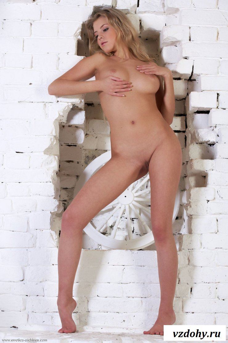 Раздетая блондинка фотографируется у стены